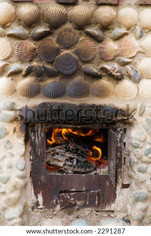 Old fireplace trimmed with a stone and a sea shell.