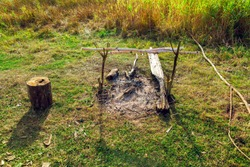 Old fireplace with hemp for sitting in a clearing in the field