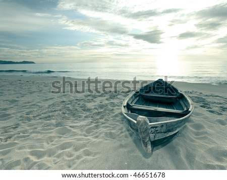 Old fisherman boat at sunrise time on the beach