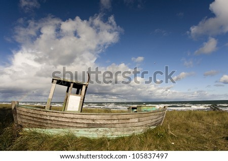 Old fisherman boat on the beach with windy sky, at baltic sea - stock photo
