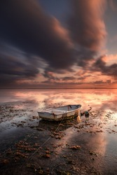 Old fisherman boat. Seascape. Fishing boat at the beach during sunrise. Low tide. Water reflection. Cloudy sky. Slow shutter speed. Soft focus. Vertical layout. Sanur beach, Bali, Indonesia.