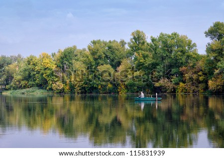 Old fisherman in boat. Calm river, early autumn. Orange, golden and green trees
