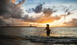 old fisherman throwing a net to catch a fish, in a sea in Bali, Indonesia