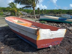 Old fishermen boats stranded on the Caribbean coast in a natural tropical environment. Old wrecked boat, stranded on the beach.