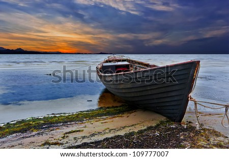 Old fishing boat at colorful sunrise