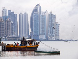 Old fishing boat in foreground with skyscrapers in background, Panama City , Panama, Central America