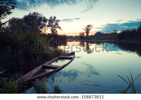 Old Fishing Boat on Lake at Sunset
