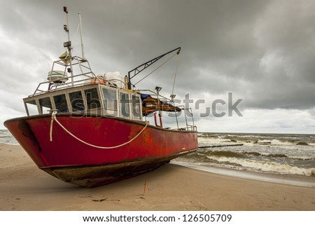 Old fishing boat on the beach in Rewal - Poland.