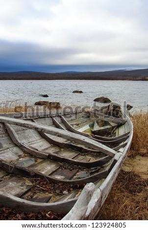 Old fishing boats on seashore - stock photo
