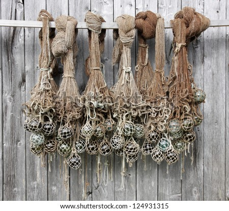 Old Fishing Nets With Glass Floats Hanging At A Boathouse