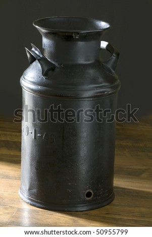 Old five gallon milk can used by dairy farmers for transporting milk from farm to market.  Sitting on an old plank floor with dark background.