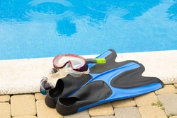 Old flippers and mask on the side of the pool. Summer. Active lifestyle.