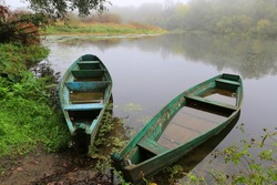 old flooded wooden boats on river