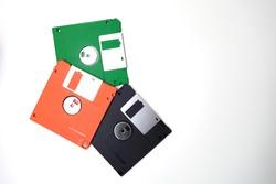 Old floppy disk isolated on white background.Floppy disk, green, orange, black