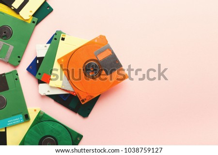 Old floppy disks isolated on pink background. Border of magnetic retro storage devices, cutout of colorful diskettes, copy space, flat lay, top view