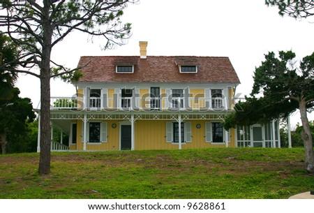 old Florida Beach House and wind-blown tree isolated against a white sky PHOTOID: Beach-House00001
