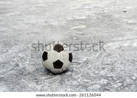 Old football ball on concrete floor background
