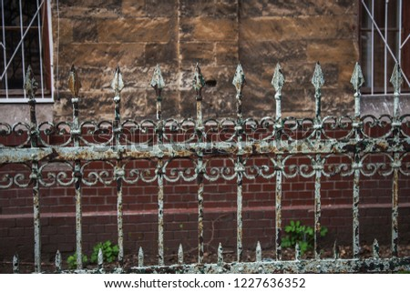 Old forged iron cast iron fence with sharp spears and cracked paint from time to time. White dirty abandoned fence that broke through the years of neglect.