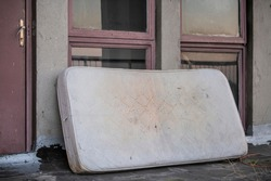 Old, forgotten, rusty, dirty mattress dumped on rooftop of residential building. Abandoned furniture. Worn out water logged mattress leaning against wall, left outside.