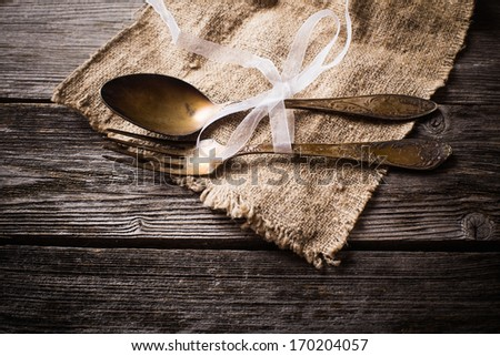 old fork and spoon on wooden...