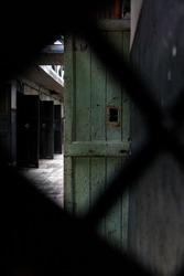 Old former prison corridor with open doors seen through the peephole of a door