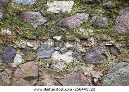 Old fortress wall made of dark gray stones with green moss, detailed background texture