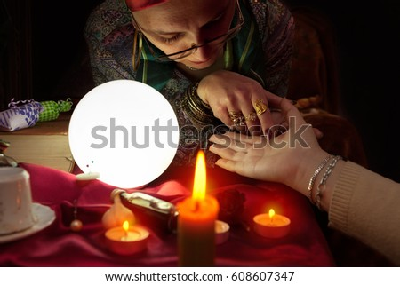 Old fortune teller woman holding another woman hand for palm reading #608607347