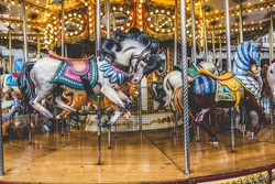Old French carousel in a holiday park. Three horses and airplane on a traditional fairground vintage carousel. Merry-go-round with horses.