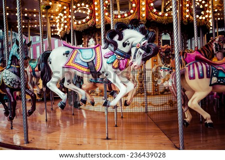 Old French carousel in a holiday park Three horses and airplane on a traditional fairground vintage carousel Merry-go-round with horses