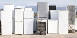 Old fridge freezer refrigerator refrigerant gas at refuse dump skip recycle stacked pile plant help environment reduce pollution white silver