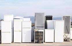 Old fridges freezers refrigerant gas at refuse dump skip recycle stacked pile plant help environment reduce pollution white silver