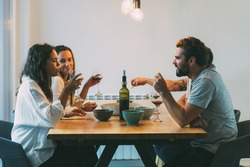 Old friends enjoying dinner and wine at home. Young men and women in casual meeting indoors. Dining room concept