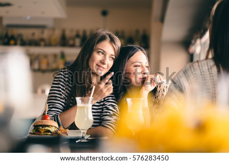 Old friends meeting up after long time for drinks and eating, talking about their memories. Girlfriends showing signs of affection, reliving beautiful moments from the past, being happy. #576283450