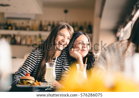 Old friends meeting up after long time for drinks and eating, talking about their memories. Girlfriends showing signs of affection, reliving beautiful moments from the past, being happy.