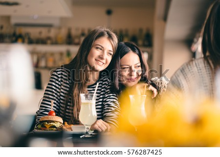 Old friends meeting up after long time for drinks and eating, talking about their memories. Girlfriends showing signs of affection, reliving beautiful moments from the past, being happy. #576287425