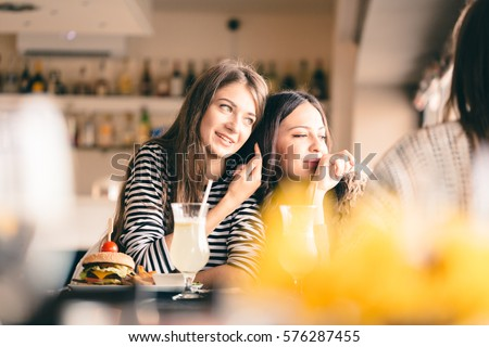 Old friends meeting up after long time for drinks and eating, talking about their memories. Girlfriends showing signs of affection, reliving beautiful moments from the past, being happy. #576287455