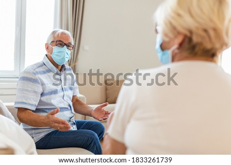 Old friends separated by social distancing on sofa at home. Senior friends wearing protective mask