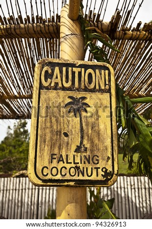 Old funny wooden caution sign on the beach.