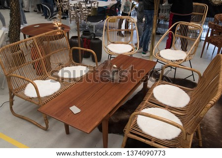 Old furniture in a living room Arrangement with a wooden coffee table in the middle surrounded by wicker 2 persons and 1 person chairs made of woven wicker. Displayed at a fair for vintage design furn