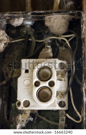 fuse box in an abandoned barn with contacts and wires covered by spider webs blowball seeds