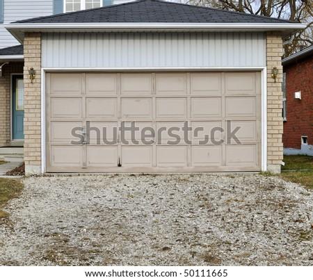 Old garage door with overgrown gravel driveway