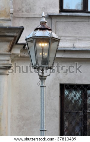 Old gas powered lamp post against wall.