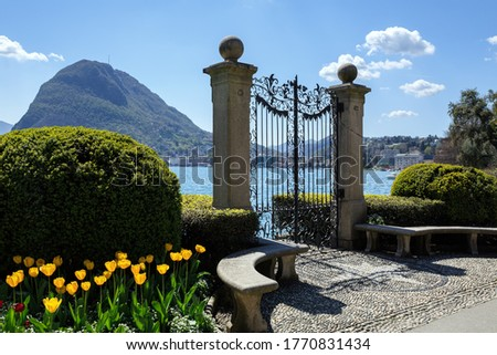 Old gate in Park Ciani at the lake Lugano on a sunny spring day. View of the San Salvatore mountain. Town of Lugano, canton of Ticino, Switzerland, Europe. Zdjęcia stock ©