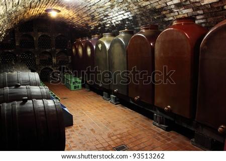 Old generic wine cellar - wooden barrels, huge ceramic containers and racks of bottles. Vintage wines.