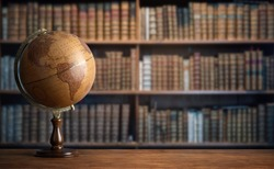 Old geographic globe in the cabinet against the background of bookselfs.Science, education, travel, vintage background. History globe and geography theme.
