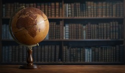 Old geographic globe in the cabinet against the background of bookselfs. Science, education, travel, vintage background. History and geography team.