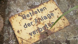 Old german, sign forbidden to enter the facility, rusted corroded metal yellow paint