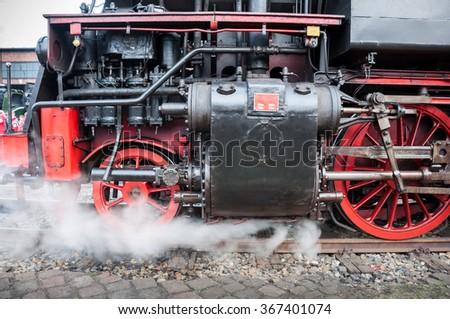 Old german steam locomotive. Detail and close up of huge wheels. #367401074