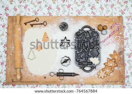 Old gingerbread maker baking sheet on wooden table with antiquities #764567884
