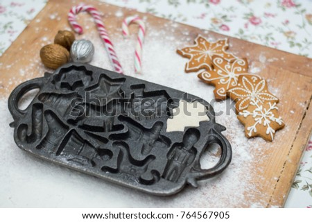 Old gingerbread maker baking sheet on wooden table with antiquities #764567905